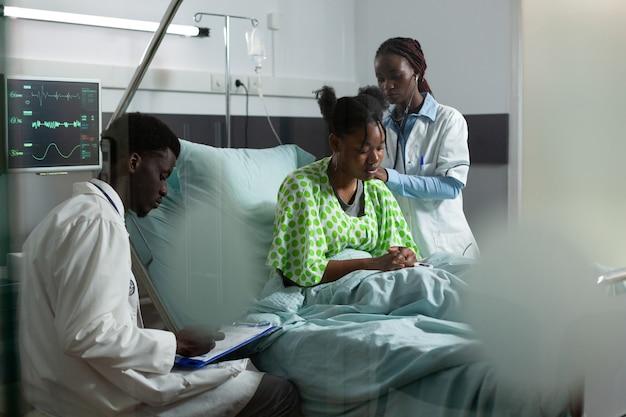 Afro-amerikaans medisch team dat werkt aan het genezen van de patiënt in het ziekenhuisbed. man en vrouw met artsenbezetting die jonge volwassene onderzoeken voor behandeling met behulp van monitor en stethoscoop