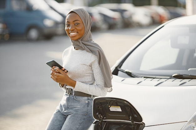 Afro-amerikaans meisje dat een elektrische auto oplaadt bij het elektrische benzinestation
