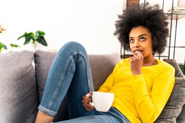 Afro-amerikaans meisje dat mok koffie drinkt en thuis ontspant