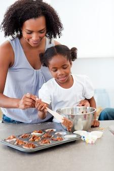 Afro-amerikaans meisje die koekjes met haar moeder voorbereiden
