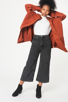 Afro-amerikaans meisje in oranje oversized jas voor fotoshoot voor jeugdkleding
