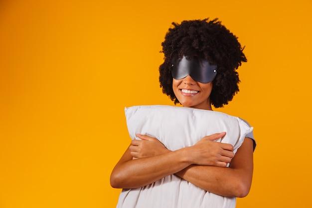 Afro-amerikaans meisje in pyjama en slaapmasker knuffelt een kussen en glimlacht, op een gele achtergrond Premium Foto