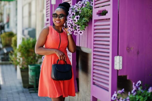 Afro-amerikaans meisje in zonnebril, perzik jurk en handtas gesteld tegen paarse ramen.