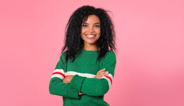 Afro-amerikaans meisje met lang rommelig ravenzwart haar in een groene jurk lacht en kijkt recht naar de cameralens
