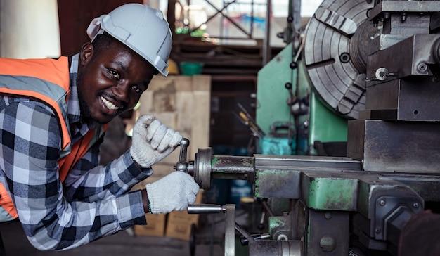 Afro-amerikaanse arbeider met witte harde helm die met machines in een fabriek werkt