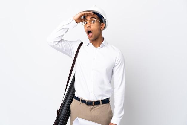 Afro-amerikaanse architect man met helm en blauwdrukken houden op geïsoleerde wit doet verrassingsgebaar tijdens het kijken naar de zijkant