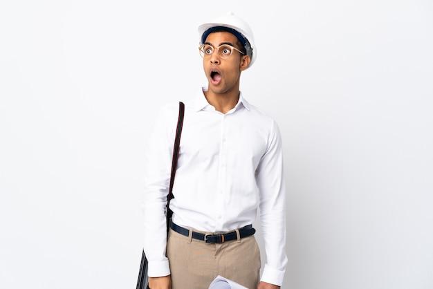 Afro-amerikaanse architect man met helm en blauwdrukken houden over geïsoleerde witte muur verrassing gebaar doen terwijl het kijken naar de kant