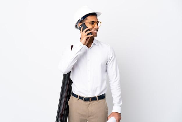 Afro-amerikaanse architect man met helm en blauwdrukken op geïsoleerde wit te houden