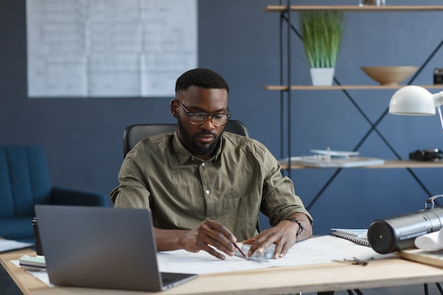 Afro-amerikaanse architect werkt op kantoor met blauwdrukkenengineer inspecteert architecturaal plan schetsin...