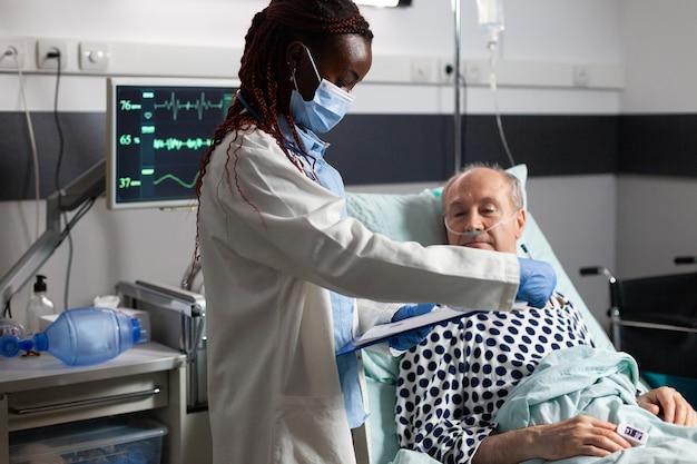 Afro-amerikaanse arts die chirurgisch masker draagt