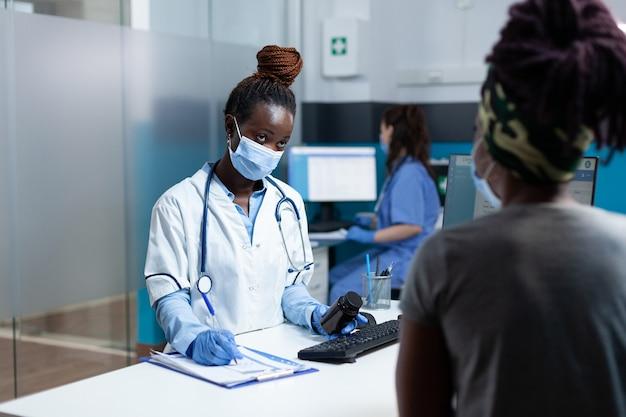 Afro-amerikaanse arts die medicamenteuze behandeling op klembord schrijft