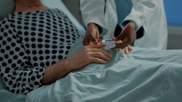Afro-amerikaanse arts die oximeter op patiënt aansluit