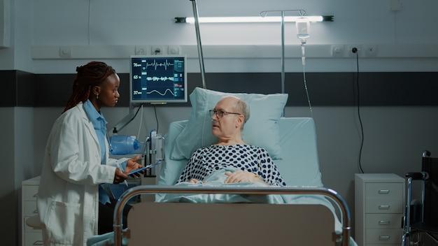 Afro-amerikaanse arts die tests controleert op zieke patiënt