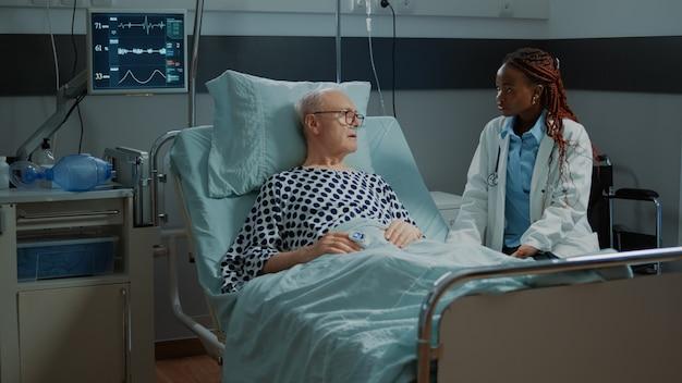 Afro-amerikaanse arts in gesprek met zieke oudere patiënt