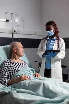 Afro-amerikaanse arts met chirurgisch masker in ziekenhuiskamer die diagnose bespreekt
