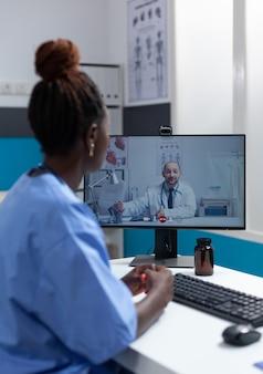Afro-amerikaanse assistent die operatiesymptomen uitlegt aan arts op afstand