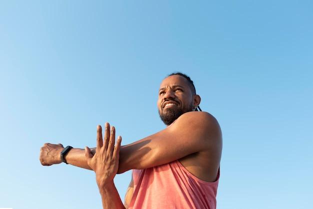 Afro-amerikaanse atleet die zich buiten uitstrekt