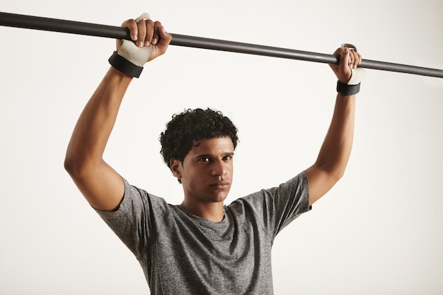 Afro-amerikaanse atleet dragen technische t-shirt en cross fitness handbescherming grijpen carbon pullup bar geïsoleerd op wit