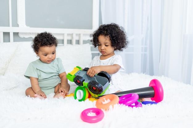 Afro-amerikaanse baby's, meisje en jongen spelen en verzamelen een kleurrijke piramide thuis op het bed