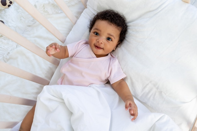 Afro-amerikaanse babyjongen in de wieg gaat naar bed of wordt 's ochtends wakker en lacht in de slaapkamer