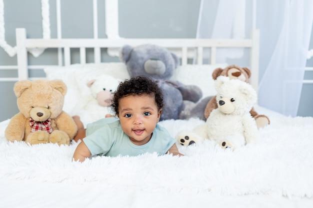 Afro-amerikaanse babyjongen zes maanden oud op bed tussen teddybeerspeelgoed