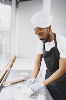 Afro-amerikaanse bakker die rauw deeg bereidt voor gebak bij het bakken. deeg kneden voor gebak