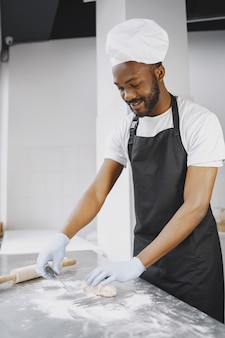 Afro-amerikaanse bakker die rauw deeg bereidt voor gebak bij het bakken. deeg kneden voor gebak Gratis Foto
