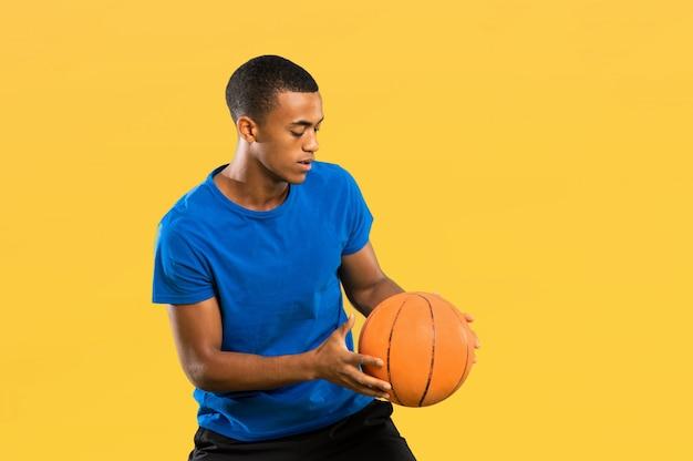 Afro amerikaanse basketbalspeler man op geel