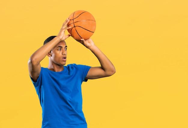 Afro amerikaanse basketbalspeler man over geel