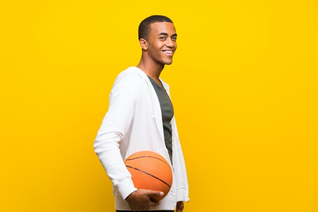 Afro amerikaanse basketbalspeler man over geïsoleerde gele achtergrond
