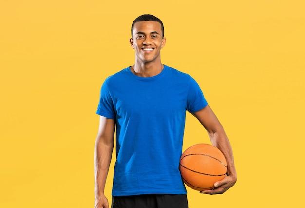 Afro amerikaanse basketbalspeler man over geïsoleerde gele muur