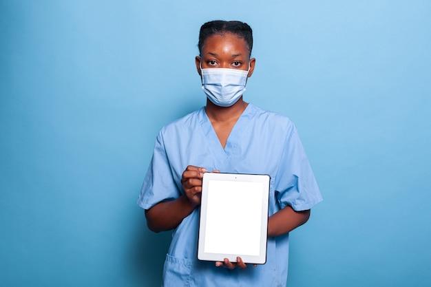 Afro-amerikaanse beoefenaar verpleegster met beschermend gezichtsmasker tegen coronavirus