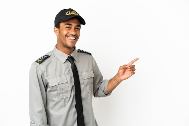 Afro-amerikaanse beveiliging over geïsoleerde witte achtergrond die met de vinger naar de zijkant wijst en een product presenteert