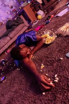 Afro-amerikaanse boozer. slapende man in zijden damespyjama rustend op walgelijk tapijt met een kom chips in de buurt