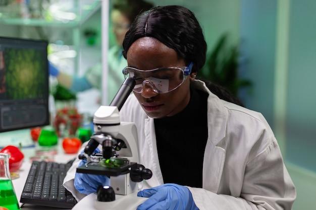 Afro-amerikaanse botanicus kijkt naar bladmonster met behulp van medische microscoop