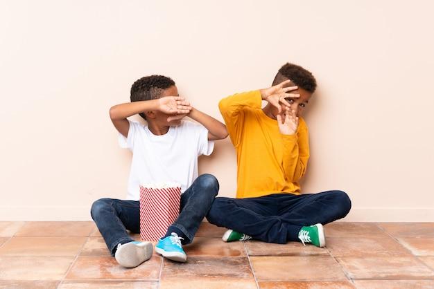 Afro-amerikaanse broers houden popcorns met angstige uitdrukking
