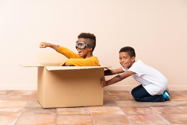 Afro-amerikaanse broers spelen. jongen in een kartonnen doos met vliegeniersglazen