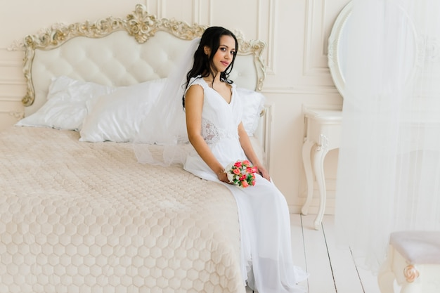 Afro-amerikaanse bruid in jurk in de ochtend die zich voorbereidt op de bruiloft in een hotelkamer
