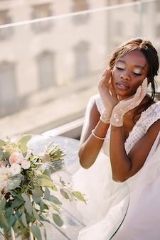 Afro-amerikaanse bruid zit aan tafel, raakt haar gezicht aan met handschoenen in haar handen, het boeket ligt op tafel