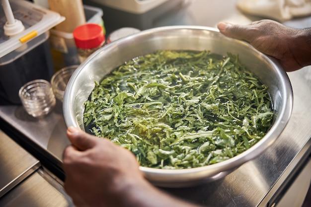 Afro-amerikaanse chef-kok met kom met groen en water op tafel