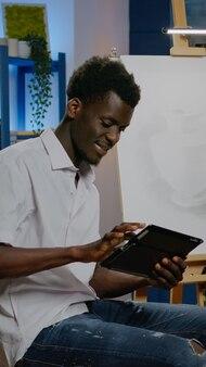 Afro-amerikaanse creatieve kunstenaar die digitale tablet gebruikt voor innovatieve creativiteit en inspiratie in kunststudioruimte. zwarte jongere met technologie die werkt aan het meesterwerk van de vaastekening