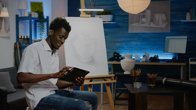 Afro-amerikaanse creatieve kunstenaar met behulp van digitale tablet