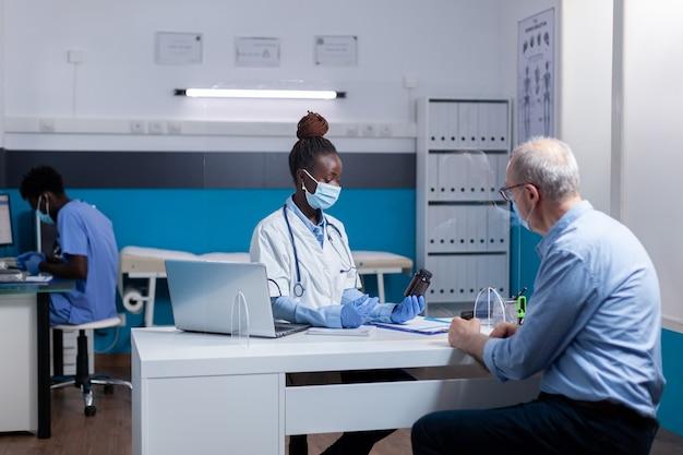 Afro-amerikaanse dokter met fles pillen met behandeling