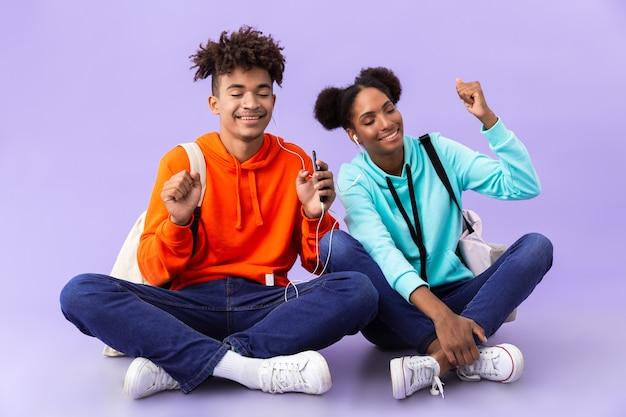 Afro-amerikaanse echtpaar draagt rugzakken met behulp van mobiele telefoon en oortelefoons zittend op de vloer met gekruiste benen, geïsoleerd over violette muur