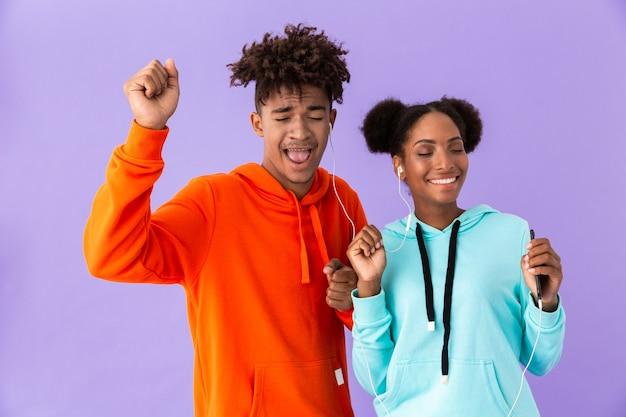 Afro-amerikaanse echtpaar in kleurrijke kleding zingen terwijl u luistert naar muziek samen met koptelefoon, geïsoleerd over violet muur