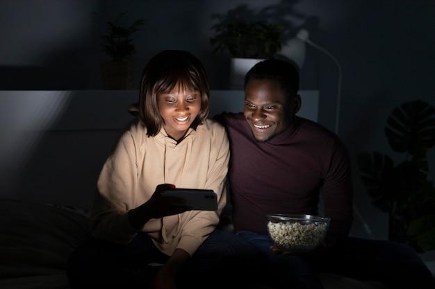 Afro-amerikaanse echtpaar kijken naar netflix samen thuis