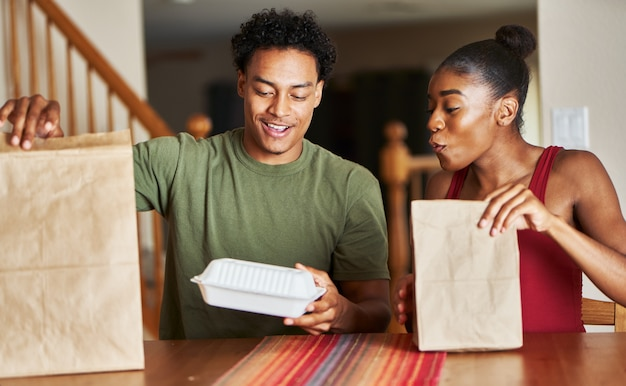 Afro-amerikaanse echtpaar zittend aan tafel kijken naar voedsel levering