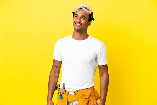 Afro-amerikaanse elektricien man over geïsoleerde gele muur die een idee denkt terwijl hij omhoog kijkt