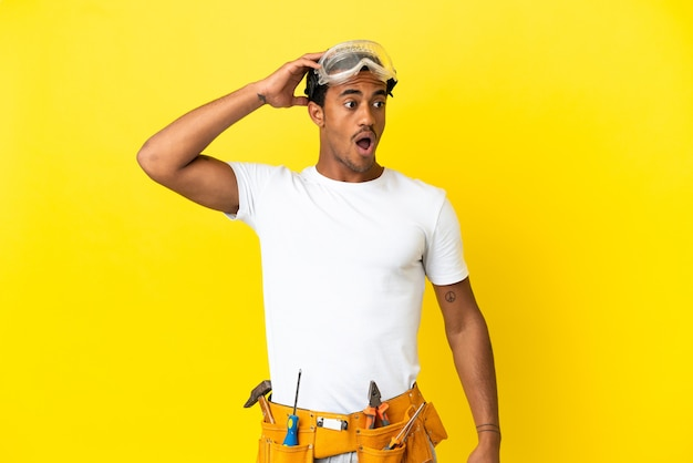Afro-amerikaanse elektricien man over geïsoleerde gele muur doet verrassingsgebaar terwijl hij naar de zijkant kijkt