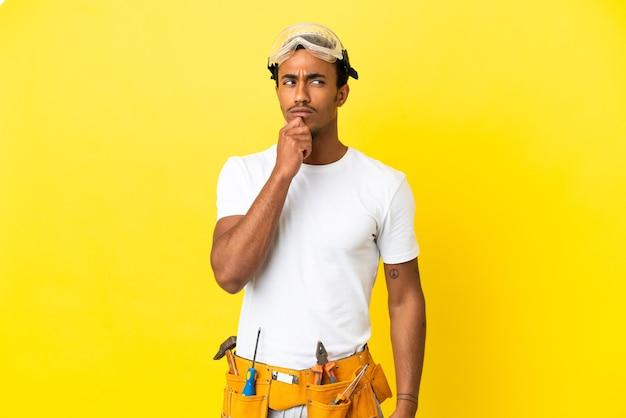Afro-amerikaanse elektricien man over geïsoleerde gele muur met twijfels en denken